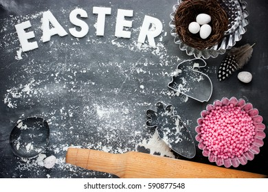 Easter festive baking composition with bird nest, candy, cookie cutter, rolling pin on black background with flour and empty space for text