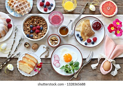 Easter festive breakfast or brunch set served on rustic wooden table. Overhead view, copy space