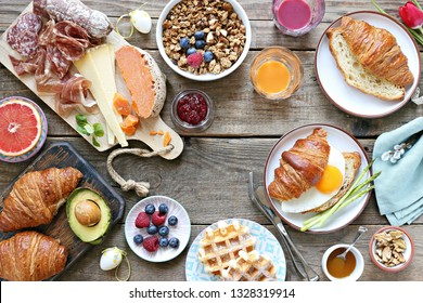 Easter festive brunch or breakfast set, meal variety with fried egg, sausage and cheese variety, croissants, granola, smoothie and dessert. Overhead view