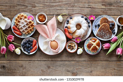 Easter festive dessert table with hot cross buns, cakes, waffles and pancakes. Overhead view
