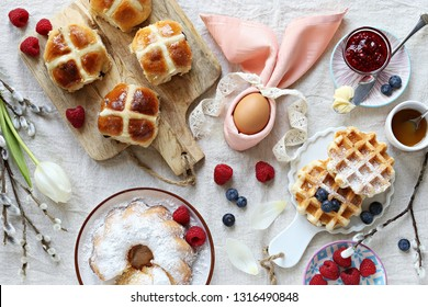 Easter festive dessert table with hot cross buns, cake and waffles on linen table cloth. Overhead view