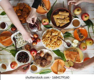 Easter festive meal on a white wooden table with homemade pastries and eggs. Healthy, natural food. Flat lay of table with hands of people eating food. View from above.