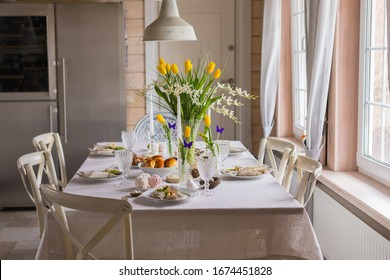 Easter festive spring table setting decoration, eggs in nest, fresh yellow tulips in vase, marshmallows, feathers, family dinner or breakfast concept, toned