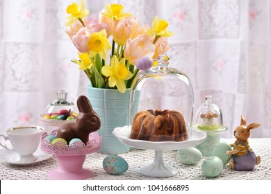 easter festive table with marble ring cake under glass dome,flowers and decorations in pastel colors