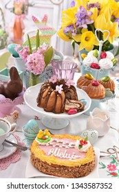 easter festive table with traditional cake called mazurek and ring cake , beautiful decorations and spring flowers