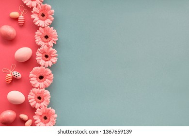 Easter flat lay in blue mint and coral colors with painted eggs and gerbera daisy flowers, copy-space