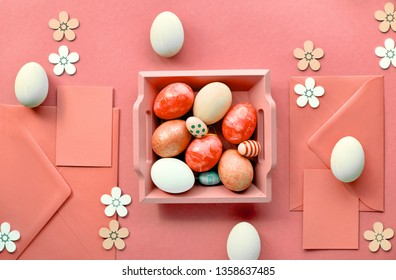 Easter flat lay in coral color with painted eggs, greeting cards, envelopes and decorative flowers