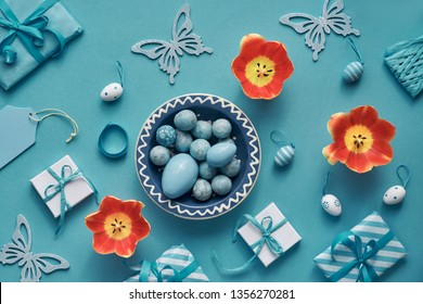 Easter flat lay in mint blue, white and orange with tulips, eggs, gift boxes and springtime decorations