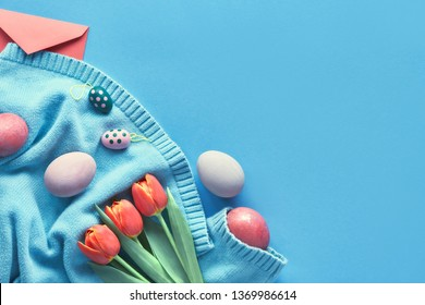 Easter flat lay on blue paper background with copy-space. Painted eggs, bunch of orange tulips and greeting envelope on mint-colored cotton sweater.
