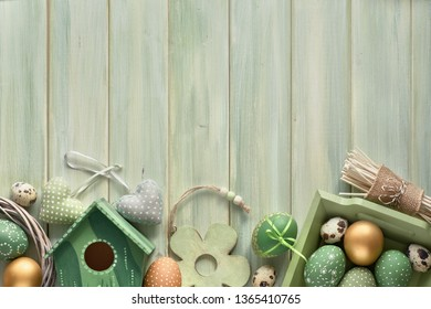 Easter flat lay on light green wooden planks with springtime decorations, eggs and nesting box, copy-space