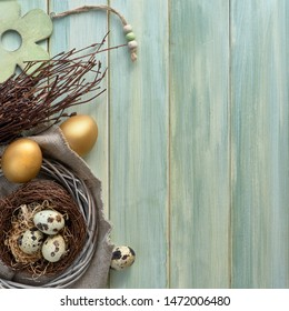 Easter flat lay on light green wooden planks with quail eggs in the nest and two golden eggs with bunch of twigs, square composition with text space