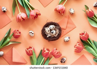 Easter flat lay on orange paper. Border made from Spring tulips, quail eggs, greeting cards and envelopes with bird nest in the middle.