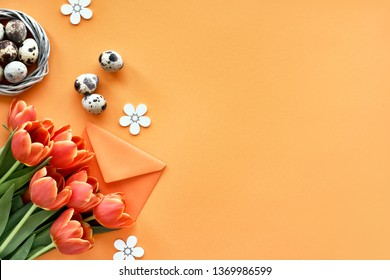 Easter flat lay on orange paper with copy-space. Quail eggs in bird nest, Spring tulips, envelope and flower decorations