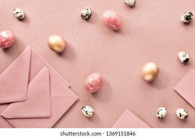 Easter flat lay on pich colored paper with quail eggs, greeting cards and envelopes
