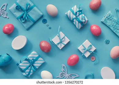 Easter flat lay in white and pink on blue mint paper background. Geometric pattern with colored eggs, gift boxes and spring decorations.