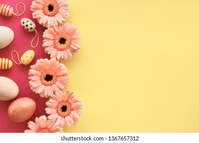 Easter flat lay in yellow and coral colors with painted eggs and gerbera daisy flowers, copy-space