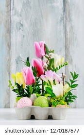 Easter floral decoration with colorful eggs, tulips, freesias and buxus.