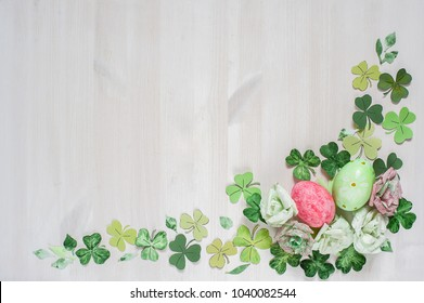 easter flower frame of cut paper  and painted eggs on white wood background