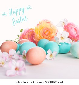 Easter and flowers background, spring concept. Blue and pink chicken eggs on white wooden table, pastel colors