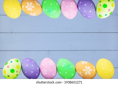 Easter frame with colored eggs on a blue wooden background.