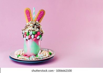 Easter freak shake decorated with bunny ears cookies topping with whipped cream and melted chocolate on pink background with copy space
