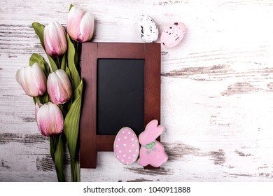 Easter gingerbread cookies, beautiful bouquet of tulips and and greeting card on wooden table.Eggs and rabbit. View from above.Copy space.