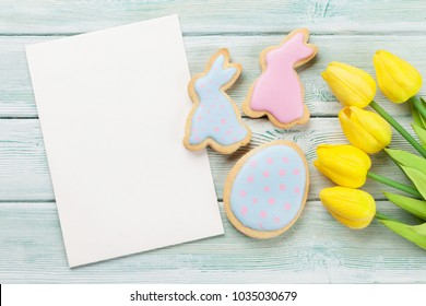 Easter gingerbread cookies and greeting card on wooden table. Eggs and rabbits. Top view with space for your greetings
