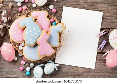 Easter gingerbread cookies on wooden table. Rabbits and eggs. Greeting card. Top view with space for your greetings