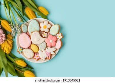 Easter gingerbread with icing on plate, seasonal flowers on blue, festive Easter background web banner, copy space. Easter card with traditional treats. Sweet Easter concept, greeting card - Shutterstock ID 1913845021