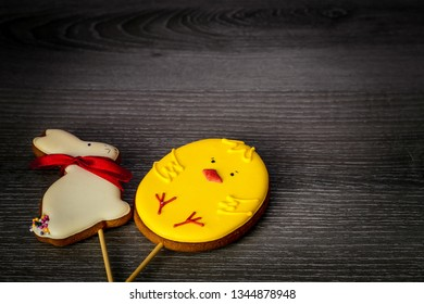 Easter gingerbread on a stick in the shape of a rabbit and in the shape of a chicken lie on a wooden table