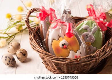 easter green and yellow wrapped cookies in a brown wicker basket near quail eggs and blossoming branch on wooden white surface