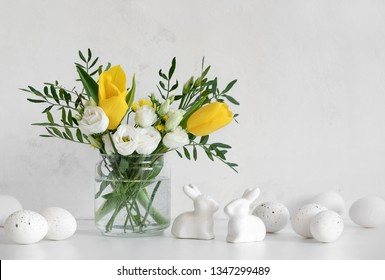 Easter greeting background, front view on white table decorated with spring flowers bouquet in a vase, Easter eggs and ceramic rabbits, blank space for a text