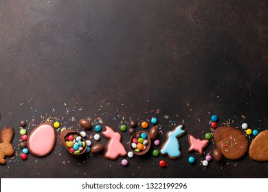 Easter greeting card backdrop with colorful gingerbread cookies, chocolate eggs and candies. Top view on stone table with space for your greetings