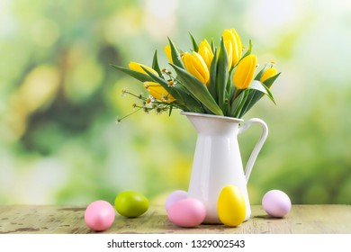 Easter greeting card with bunch of tulips and easter eggs in a summer garden. Copy space