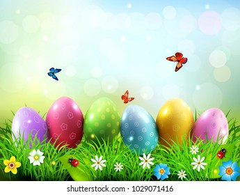 Easter greeting card with colorful eggs lying on the green grass against the blue sky. Design element, greeting card template