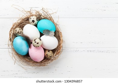 Easter greeting card with colorful eggs in nest on white wooden table. Top view with space for your greetings - Shutterstock ID 1304396857
