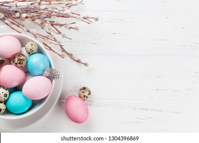 Easter greeting card with colorful eggs in bowl on white wooden table. Top view with space for your greetings