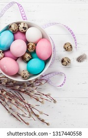 Easter greeting card with colorful easter eggs in bowl on wooden table. Top view with space for your greetings