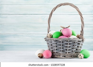Easter greeting card with colorful easter eggs in basket. In front of wooden wall with space for your greetings