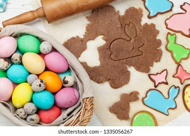 Easter greeting card with cooking gingerbread cookies and colorful eggs. Top view