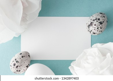 Easter greeting card with eggs and white roses on blue background