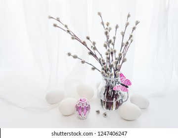 Easter greeting card. Fluffy pussy-willow branches in a transparent glass pitcher, pink batterfly and white end pink Easter eggs against a white transparent cloth