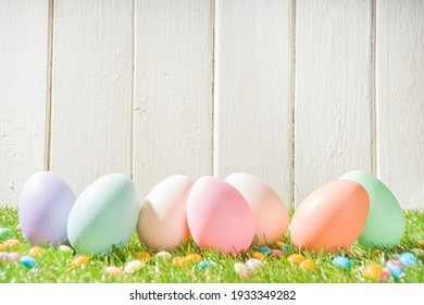 Easter Greeting card, invitation background. Easter Eggs In A Row on Spring Grass and White Wooden Background