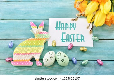 "easter greeting card with text ""happy easter "",colorful rabbit,eggs and bunch of tulips on blue wooden background"