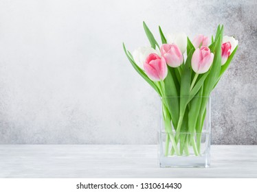 Easter greeting card with tulip flowers bouquet. In front of stone wall with space for your greetings