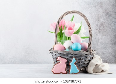 Easter greeting card with tulip flowers, gingerbread cookies and easter eggs. In front of stone wall with space for your greetings