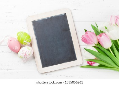 Easter greeting card with tulip flowers and easter eggs. Top view on wooden table with chalkboard for your greetings