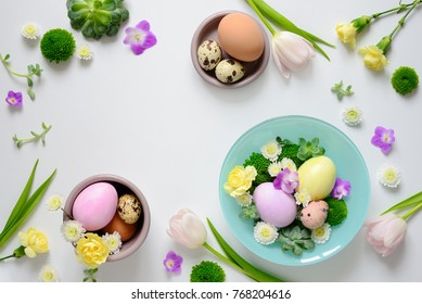 Easter greeting floral background with a space for a text, decorative arrangement with pastel colored hand painted eggs and spring flowers, view from above, flat lay