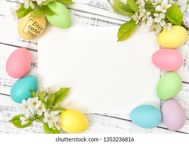 Easter greetings card, decoration and spring flowers. Pastel colored egg on bright wooden background