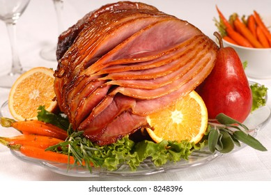 An Easter ham glazed with brown sugar and honey served with carrots, fruit and herbs